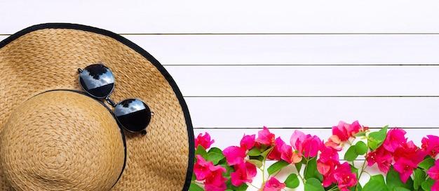 Letni kapelusz z okularami przeciwsłonecznymi i różowym kwiatem bugenwilli na fakturze drewna
