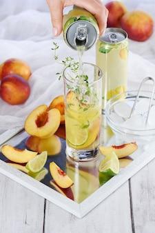 Letni koktajl brzoskwiniowy. orzeźwiający organiczny napój bezalkoholowy, lemoniada z dojrzałym nektarynką, tymiankiem i limonką