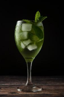 Letni koktajl lub napój w kieliszku do wina. orzeźwiający napój z liśćmi mięty, tonik dżinowy, syrop.