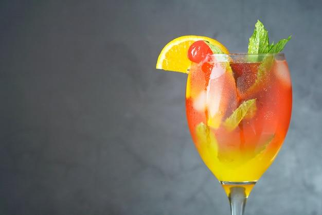 Letni koktajl. sok pomarańczowy z miętą, syropem, kawałkami owoców i wiśnią z lodem.