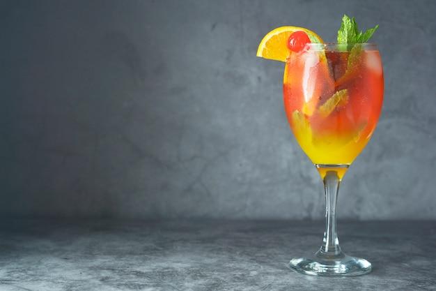 Letni koktajl. sok pomarańczowy z miętą, syropem, plastrami owoców i wiśnią z lodem.