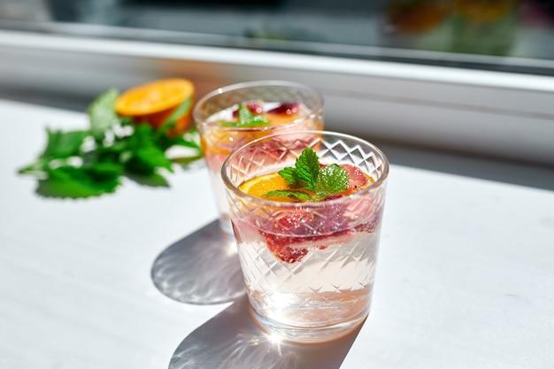 Letni koktajl z truskawek, pomarańczy i mięty w szkle na białym stole