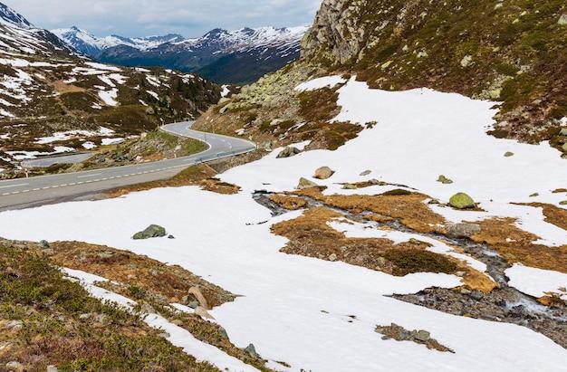 Letni krajobraz górski alp z alpejską drogą i małym strumieniem (przełęcz fluela, szwajcaria)
