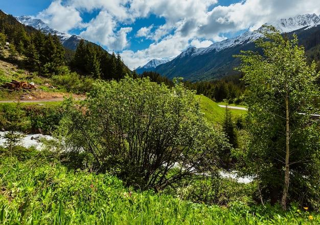 Letni krajobraz górski alp z alpejską rzeką i drogą (alpy silvretta, austria).