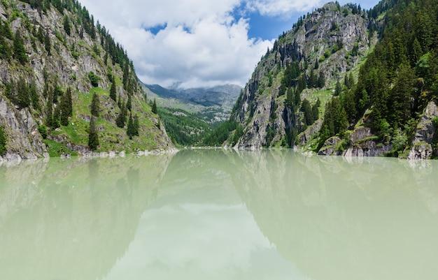 Letni krajobraz górski alp z mętnym jeziorem i stromymi skalistymi zboczami, szwajcaria