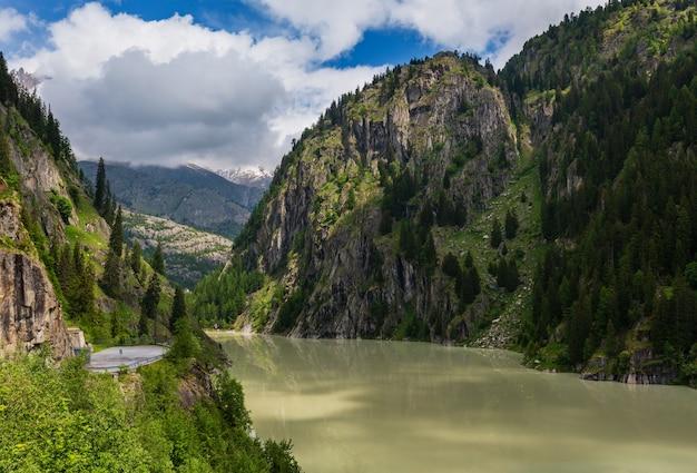 Letni krajobraz górski alp z mętnym jeziorem zbiornik wodny i stromymi skalistymi zboczami, szwajcaria