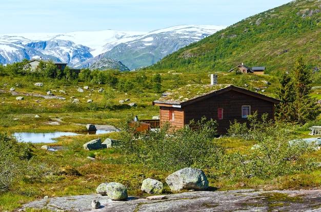 Letni krajobraz górski z drewnianym domem.