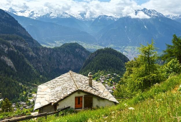 Letni krajobraz górski ze śniegiem na szczycie góry i domem na zboczu (alpy, szwajcaria)