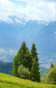 Letni krajobraz górski ze śniegiem na szczycie góry i miastem w dolinie (alpy, szwajcaria)