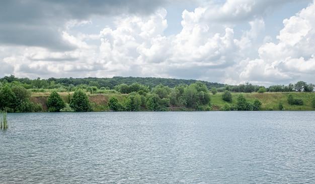 Letni krajobraz na wsi z rzeką, lasem i chmurami.