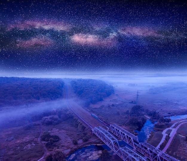 Letni krajobraz nocny, kolej przez las. gwiaździste niebo.