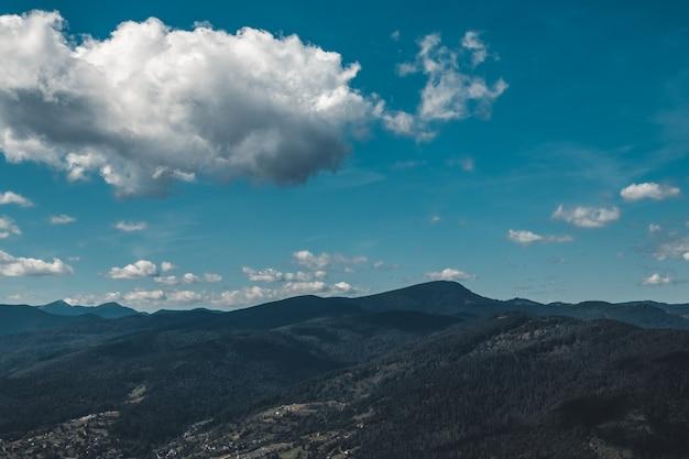 Letni krajobraz w górach i ciemne błękitne niebo z chmurami
