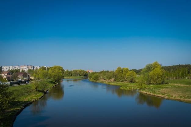 Letni krajobraz wiejski z rzeką i niebieskim tle nieba.