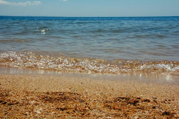 Letni krajobraz z falami morskimi docierającymi do brzegu morza