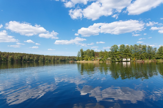 Letni krajobraz z jeziorem, otoczony lasem z domem i molo na brzegu.