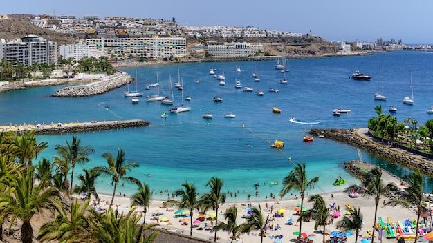 Letni krajobraz z plażą, na której kąpią się ludzie, hotele i łodzie zakotwiczone w morzu. wyspy kanaryjskie. arguineguin. hiszpania,