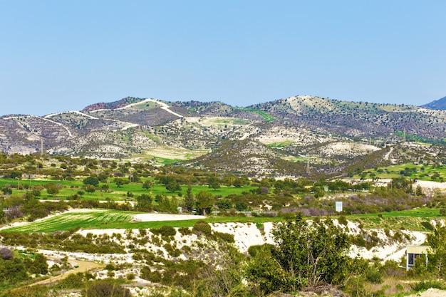 Letni krajobraz z zieloną trawą, wzgórzami i górami