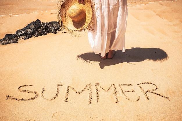 Letni ludzie podróżują koncepcję wakacji wakacyjnych z młodą kaukaską piękną kobietą na plaży, ciesząc się słońcem ze słowem lato napisanym na piasku
