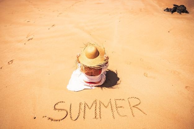 Letni ludzie podróżują koncepcję wakacji wakacyjnych z młodą kaukaską piękną kobietą, siedząc na plaży, ciesząc się słońcem ze słowem lato napisanym na piasku