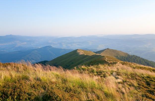 Letni mglisty górski krajobraz z krzyżem chrześcijańskim na szczycie (ukraina, karpaty)