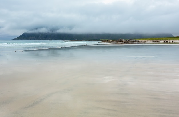 Letni mglisty i pochmurny widok na plażę z białym piaskiem i odbiciami nieba w ramberg (norwegia, lofoty).