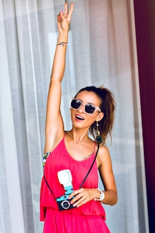 Letni moda portret młodej kobiety, pozowanie, uśmiechając się i bawiąc się, ubrany w stylowy kombinezon neon i okulary przeciwsłoneczne, trzymając zabawny aparat retro. pokazuje naukę o kawałkach.
