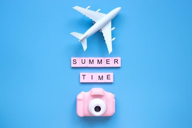 Letni model samolotu i różowy aparat na niebieskim tle koncepcja podróży travel