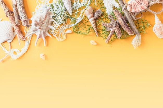 Letni motyw relaksacyjny z muszelkami, kapeluszem, okularami przeciwsłonecznymi i aparatem na żółtym