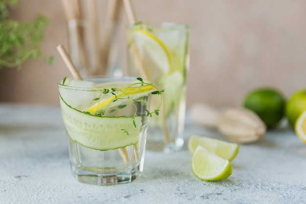 Letni napój alkoholowy. domowy orzeźwiający koktajl z ginem, wódką lub tequilą, ogórkiem, limonką, kostkami lodu i tymiankiem