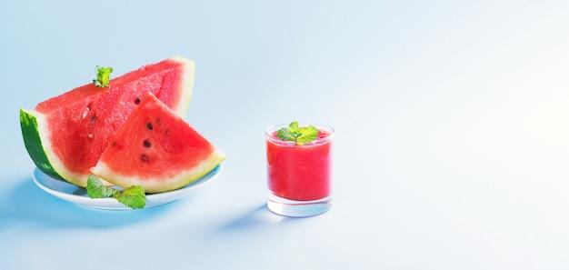 Letni napój, arbuzowy koktajl w szklance ze świeżymi plasterkami arbuza na talerzu na pastelowym niebieskim tle, letni zdrowy napój owocowy