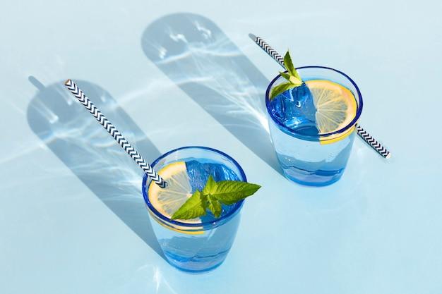 Letni napój. chłodny orzeźwiający napój z miętą i cytryną w szklance. zero odpadów w domu. minimalizm. naturalna świeża lemoniada z twardymi cieniami na niebieskim tle