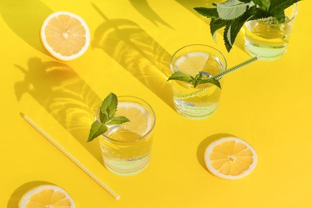 Letni napój. chłodny orzeźwiający napój z miętą i cytryną w szklance. zero odpadów w domu. minimalizm. świeża lemoniada z twardymi cieniami na żółtym tle