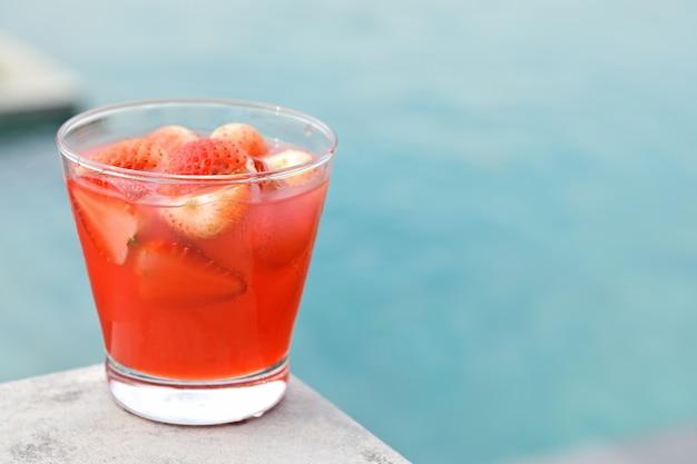 Letni napój truskawkowy na granicy basenu