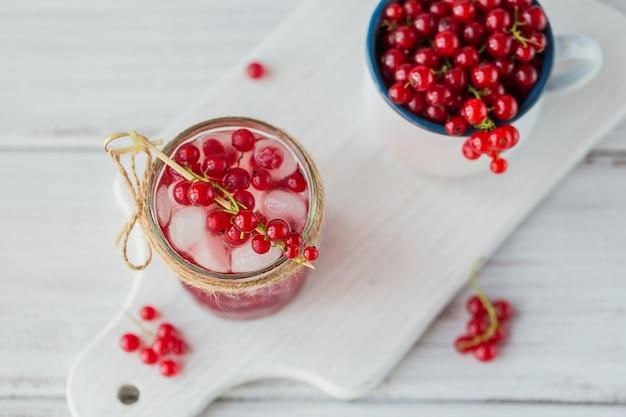 Letni napój z białym winem musującym. domowy orzeźwiający koktajl owocowy lub poncz z szampanem, czerwoną porzeczką i kostkami lodu na białym drewnianym drewnianym stole.