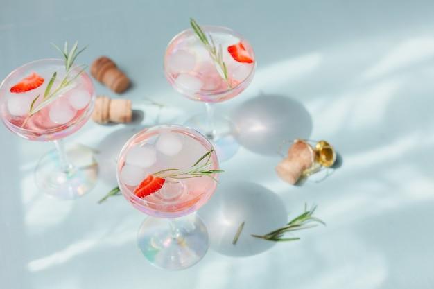 Letni napój z białym winem musującym. domowy orzeźwiający koktajl owocowy lub poncz z szampanem, truskawkami, kostkami lodu i rozmarynem
