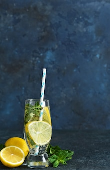 Letni napój z cytryną i miętą na ciemnym stole.