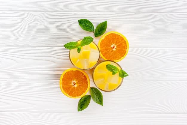 Letni napój z pomarańczy z lodem na białym drewnianym