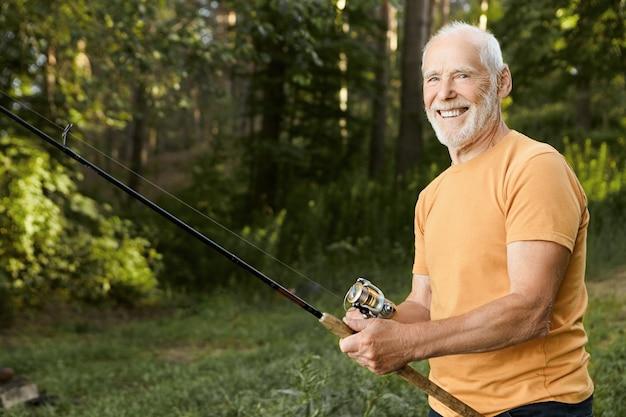 Letni obraz doświadczonego rybaka na emeryturze odpoczywającego na dzikiej przyrodzie na wędkę, czekającego na złowienie ryb