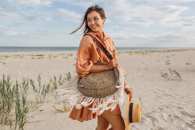Letni obraz pięknej brunetki kobiety w modnej lnianej sukience, skacząc i wygłupiając się, trzymając słomkową torbę. dość szczupła dziewczyna korzystających z weekendów w pobliżu oceanu.