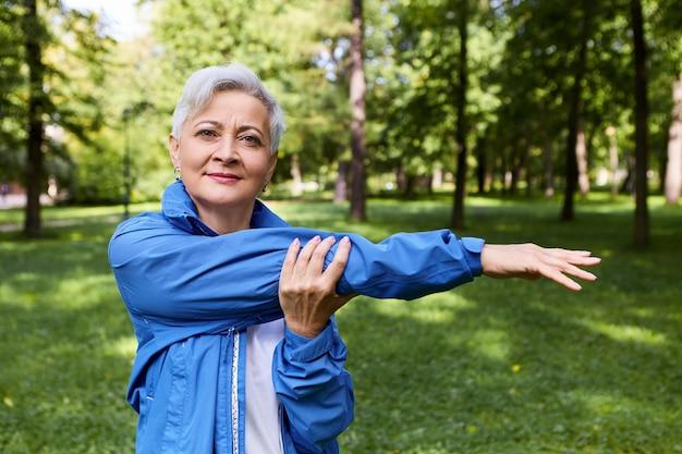 Letni obraz zdrowej, aktywnej kobiety na emeryturze, uśmiechnięta, rozciągająca mięśnie ramion po uruchomieniu treningu na świeżym powietrzu, pozowanie w lesie. zdrowie, dobre samopoczucie, wiek, ludzie, sport i koncepcja aktywności