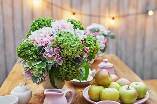 Letni ogród w tle. bukiet kwiatów hortensji i filiżankę herbaty na stole. dobry przytulny poranek. piknik na łonie natury. kartkę z życzeniami na dzień matki. uroczystość