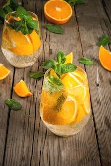 Letni orzeźwiający napój pomarańczowy. detox, dieta, podawana w infuzji. wariacje na temat lemoniady. woda mineralna z kawałkami świeżej pomarańczy i mięty. na rustykalnym drewnianym stole. pionowa, kopia przestrzeń