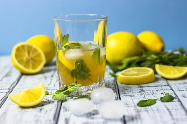 Letni orzeźwiający napój w szklance. tradycyjna zimna słodko-kwaśna lemoniada z cytryną, miętą i kostkami lodu na szarym drewnianym stole.