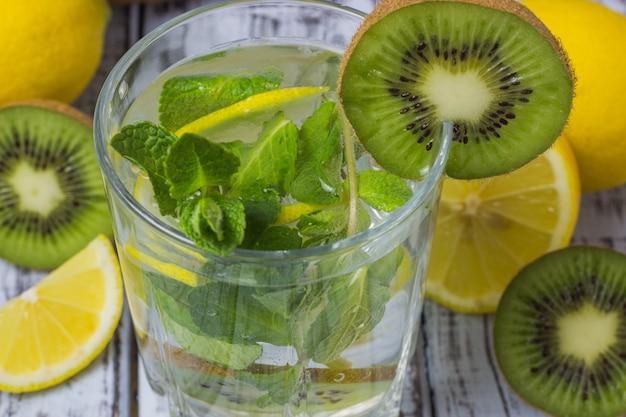Letni orzeźwiający napój w szklance z bliska słomy. zimna słodko-kwaśna lemoniada z kostkami cytryny, kiwi, mięty i lodu na szarym drewnianym stole.