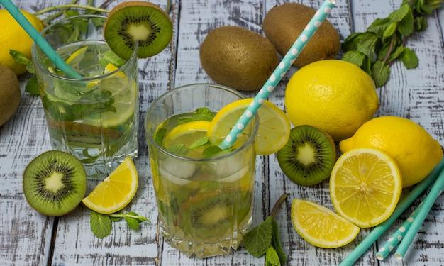Letni orzeźwiający napój w szklankach ze słomką. zimna słodko-kwaśna lemoniada z cytryną, kiwi, miętą i kostkami lodu na szarym drewnianym stole.