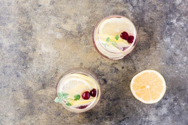 Letni orzeźwiający zimny koktajl z cytryną, melisą i wiśniowo-twardym seltzerem w szklankach na stole. widok z góry