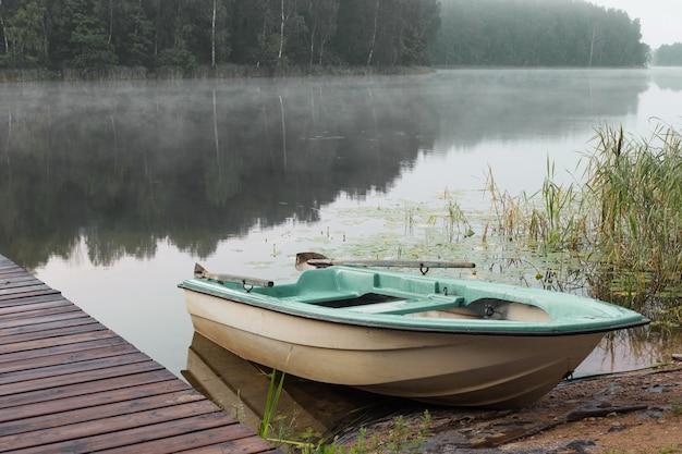 Letni piękny krajobraz z łodzią na jeziorze o wschodzie słońca