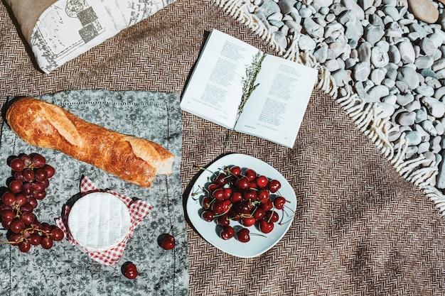 Letni piknik na kratę z bagietką wiśnie ser otwarta książka
