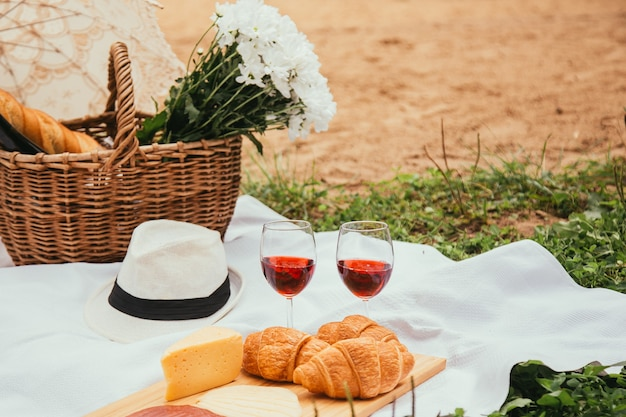 Letni piknik na plaży o zachodzie słońca w koncepcji jedzenia i picia w białą kratę