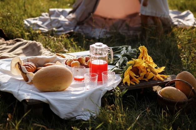 Letni piknik. na stole są melon, sok, kwiaty. letni wieczór